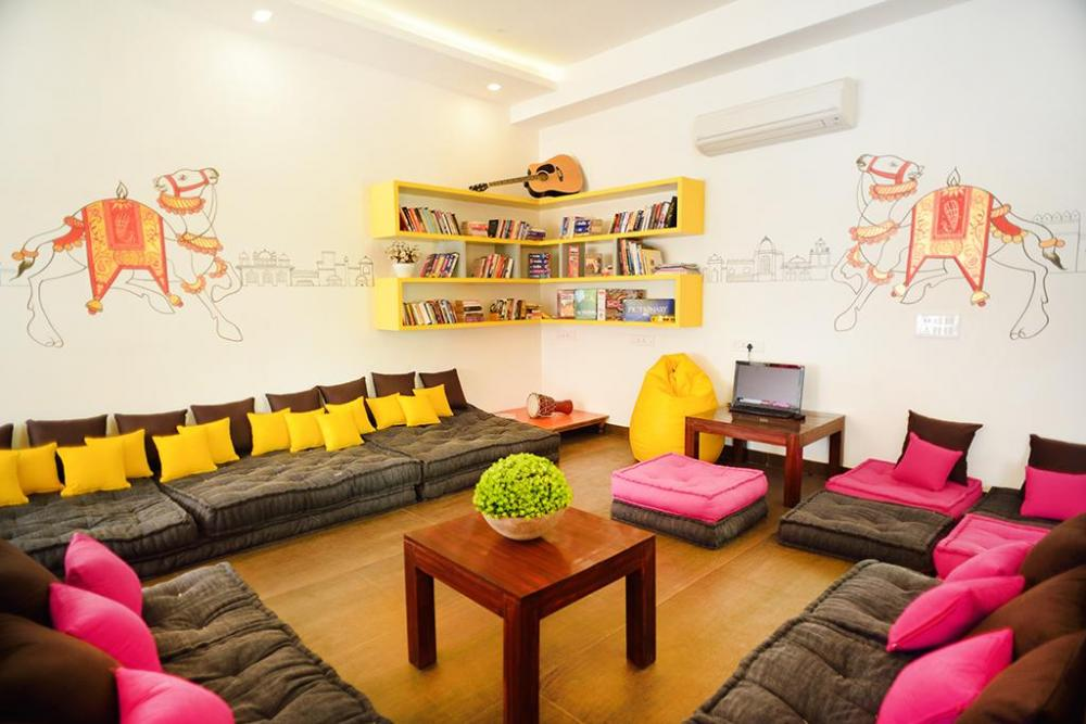 The colorful common room with comfortable seating and a small library.