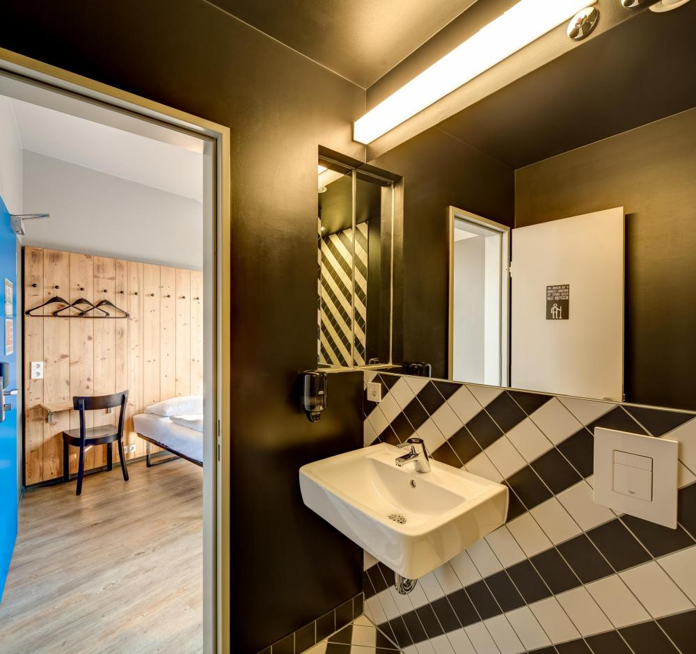 sample bathroom and twin bedding in room
